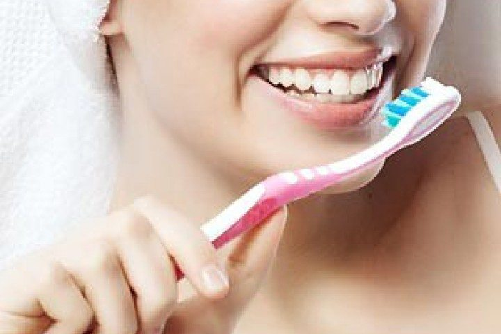 Woman with a toothbrush, Franklin, TN dentist office, best family and cosmetic dentistry, Zoom! in-office whitening and teeth whitening.
