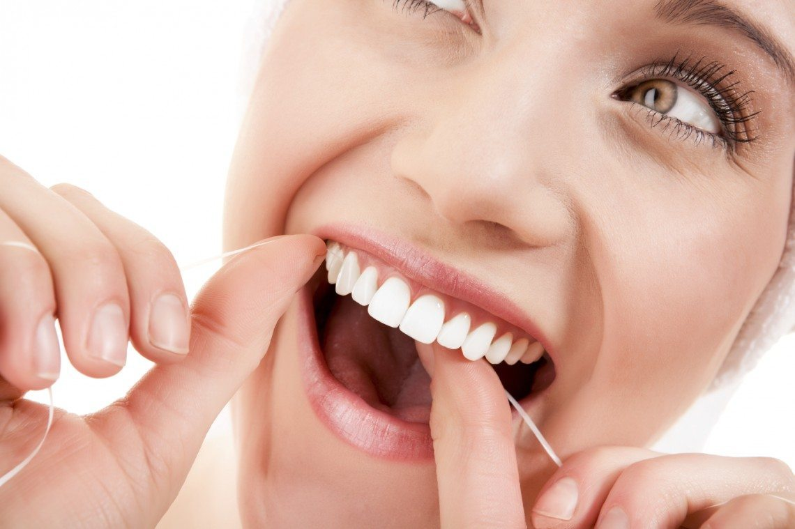 Woman flossing, Franklin, TN dentist office, the best family and cosmetic dentists, Zoom! in-office teeth whitening, best dentist Franklin, TN..